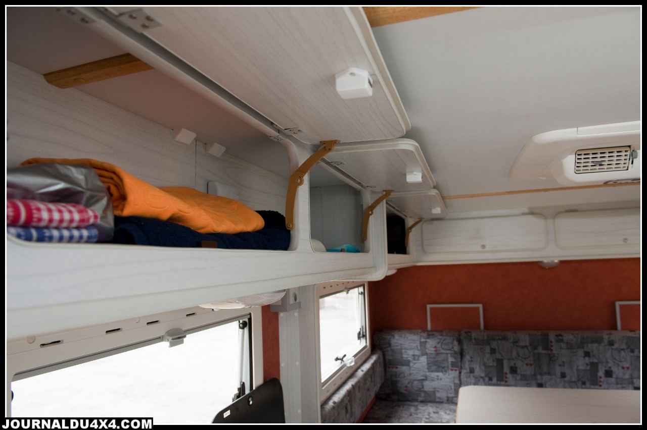Des coffres sont disposés en hauteur, le 4x4 a aussi des placards sous l'évier ainsi que des coffres sous les sièges, tout un tas de rangements pour embarquer le nécessaire de voyage.