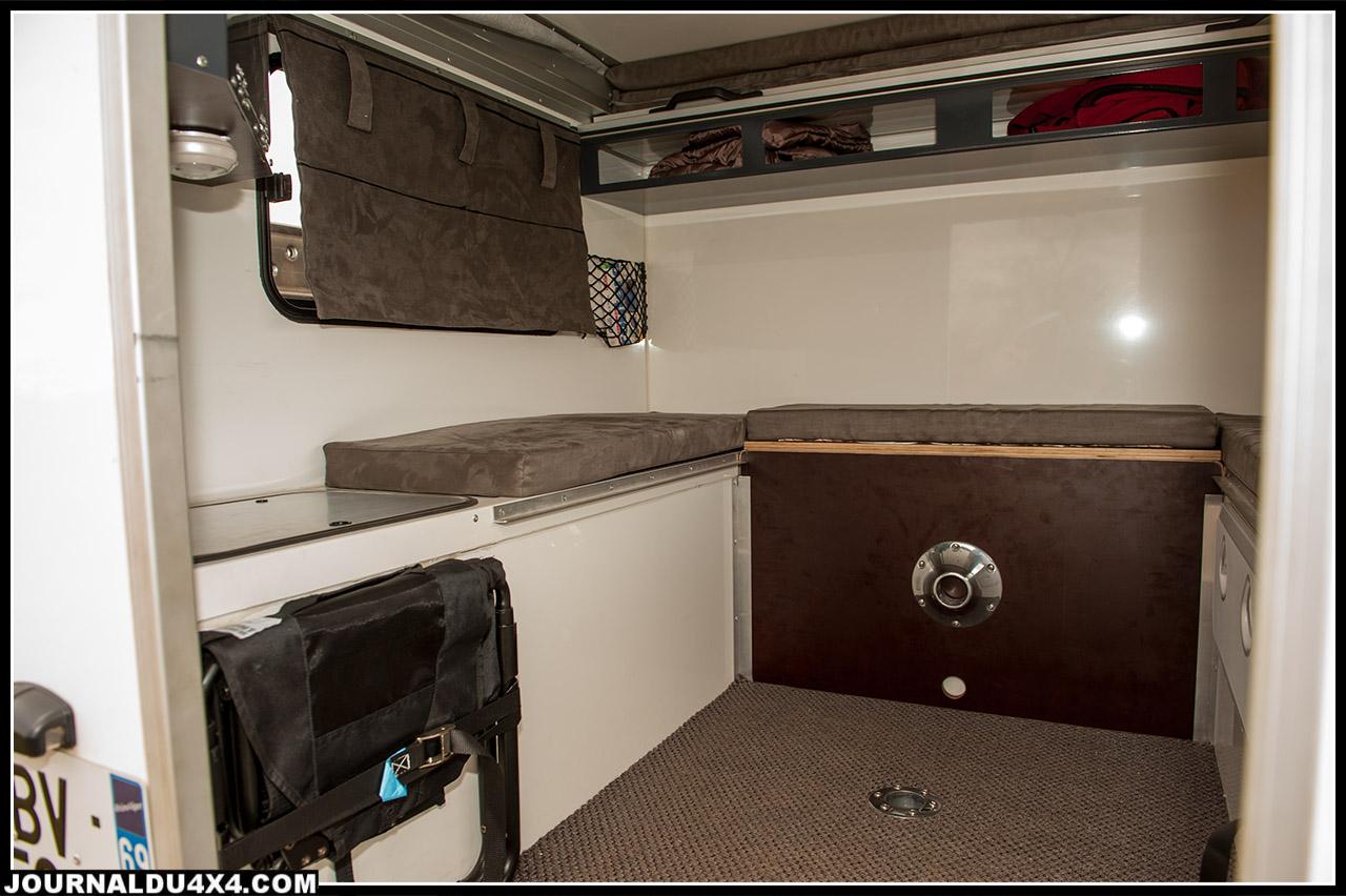 Vue de l'intérieur de la cellule. A gauche, un fauteuil de camping est attaché mais facilement accessible, au fond verticalement se trouve le plateau de la table est rangé.