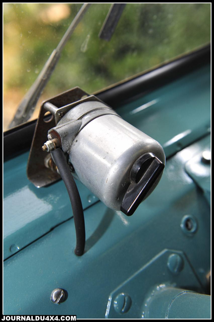 Pas la peine d'user les piles, les deux moteurs d'essuis glace fonctionnent séparément. Pas difficile à identifier, c'est le n°586 de JA2 produit à Aurillac. Un vrai Cournil made in Cantal! Question, comment ça marche? Rien de plus simple avec les 3 vitesses de la boîte de Jeep M38A1. Il suffit ensuite d'engager le pont avant et de passer en courte…Bras musclés indispensables.