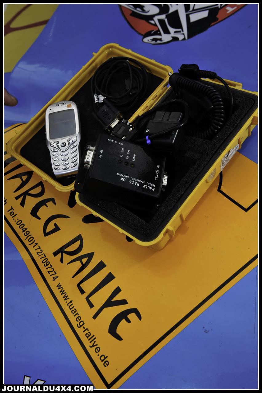 """L'électronique moteur vous fait encore peur?  Mike Jones alias """"Beady"""" a résolu le problème. Tous les Desert Warrior  sont livrés avec la petite mallette à malice. Elle contient un vieux téléphone portable chargé du programme RaBe (BMW diagnostic) et sa connectique réservée aux situations les plus compliquées. Dans la majorité des cas, il suffit de brancher le petit module fourni sur la prise diagnostique du moteur qui se chargera d'annuler automatiquement les principaux codes pannes moteur connus et de rallier l'arrivée."""