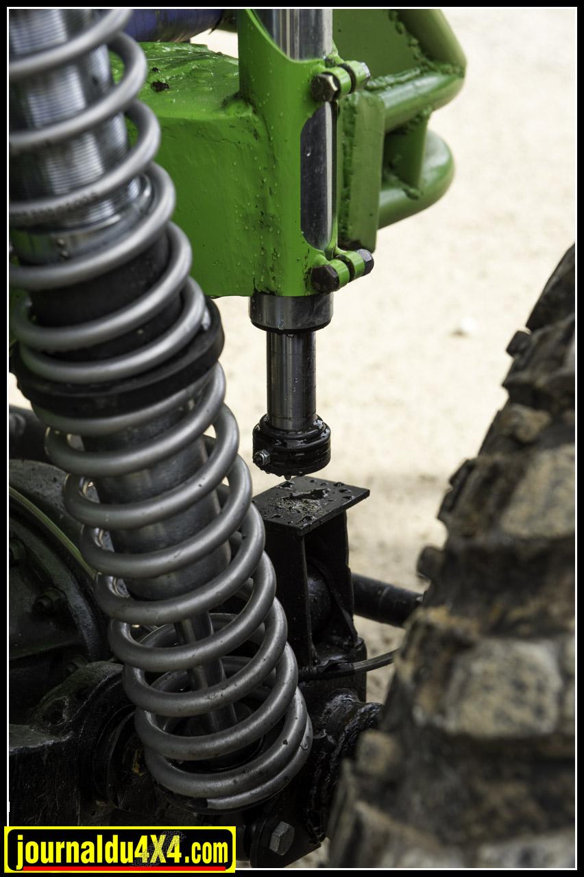 les amortisseurs entourés par les ressorts se nomment : coilover. Le corps fileté qu'on aperçoit en haut permet de régler la dureté de ressorts. On aperçoit aussi le bumpstop qui fait office de tampon; d'amortisseur pour le pont en cas de chocs en compression.