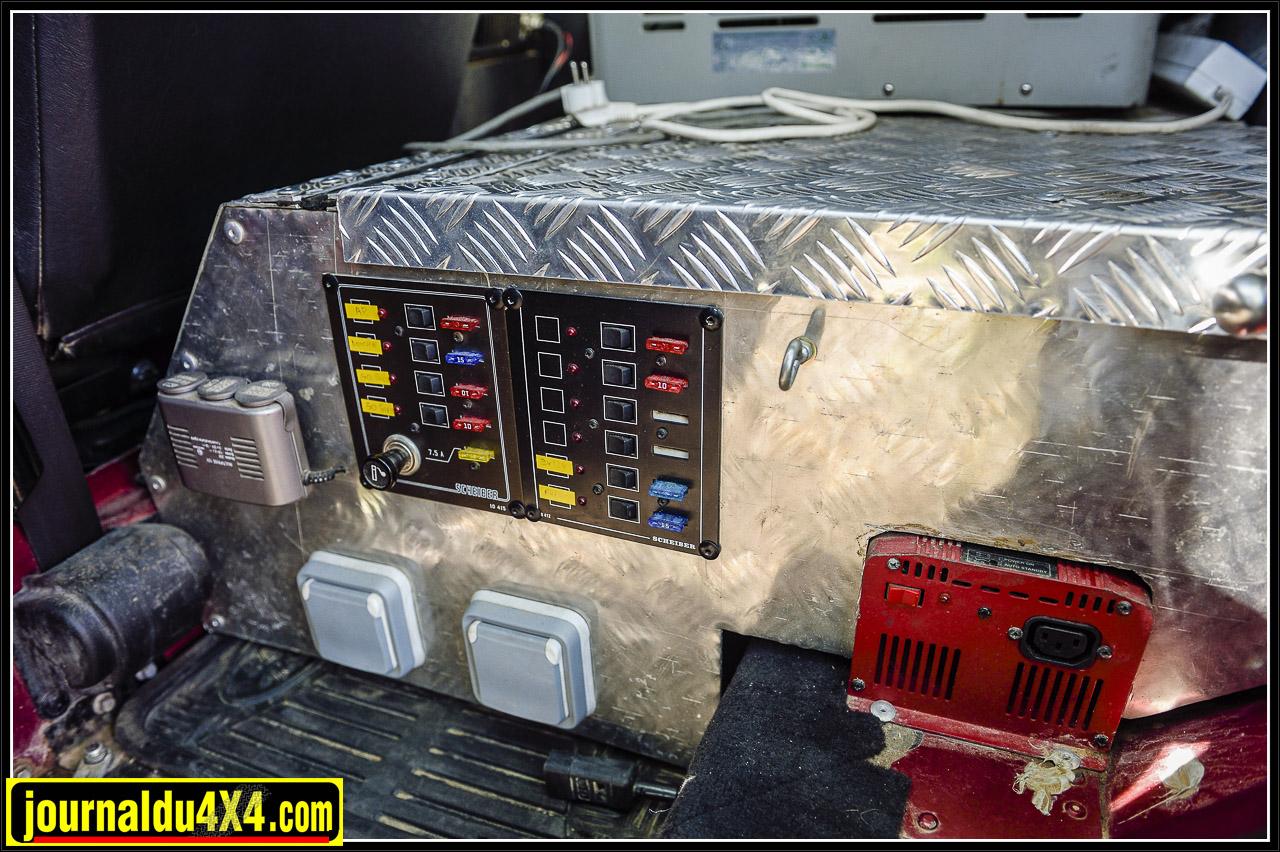 prises 12 V, deux prises 220 V et un tableau électrique avec fusibles et interrupteurs