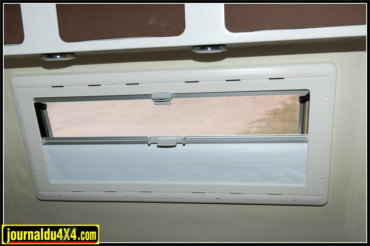 Fenêtres équipées d'un rideau occultant et d'une moustiquaire