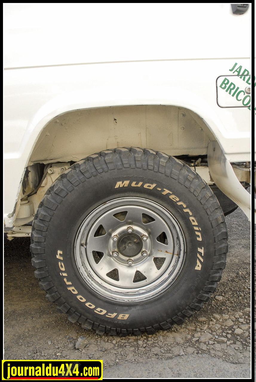 Les pneumatiques sont les classiques BF Goodrich en 235/85 x 16 Mud Terrain sur des jantes tôles chromées Triangular.