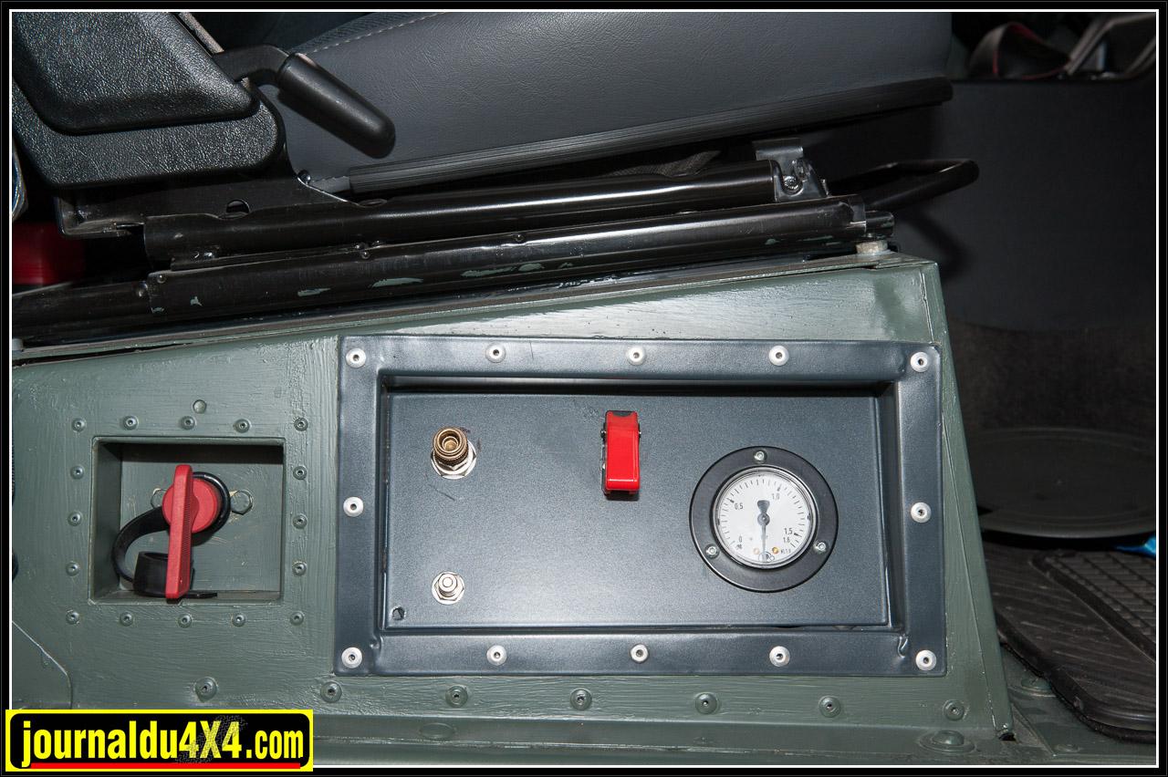 Sous le siège du passager, nous retrouvons un coupe-circuit, l'interrupteur du compresseur, le manomètre et le raccord du tuyau d'air