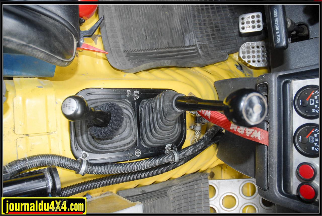 Entre les deux siéges baquet  en skaï qui ne craigne pas la boue, on retrouve levier de boîte manuelle, de transfert d'origine à pont avant enclenchable du Hilux Toy et la prise de télécommandes du treuil.