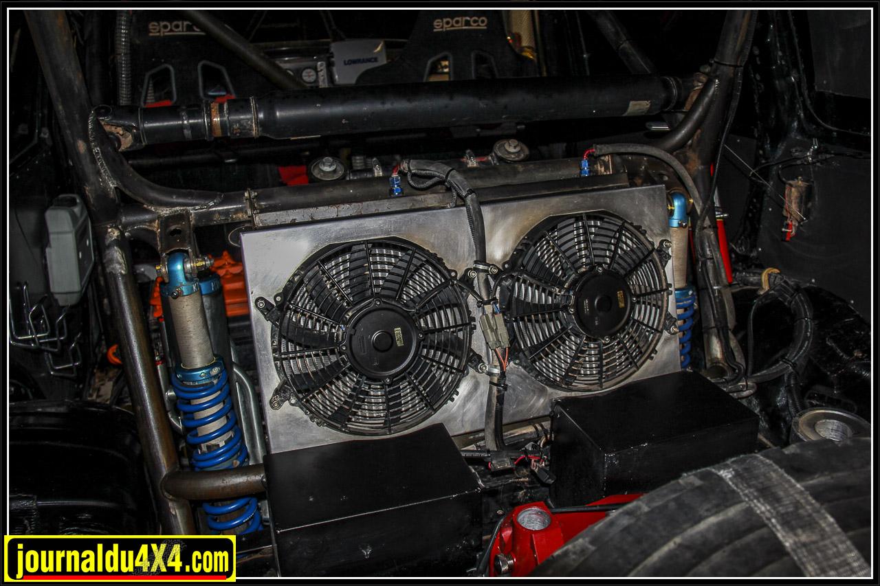 Le radiateur de refroidissement de la transmission est équipé de deux ventilateurs électriques. Juste devant sur la photographie, on distingue deux boites noires dans lesquelles se trouvent les batteries afin de bien les protéger