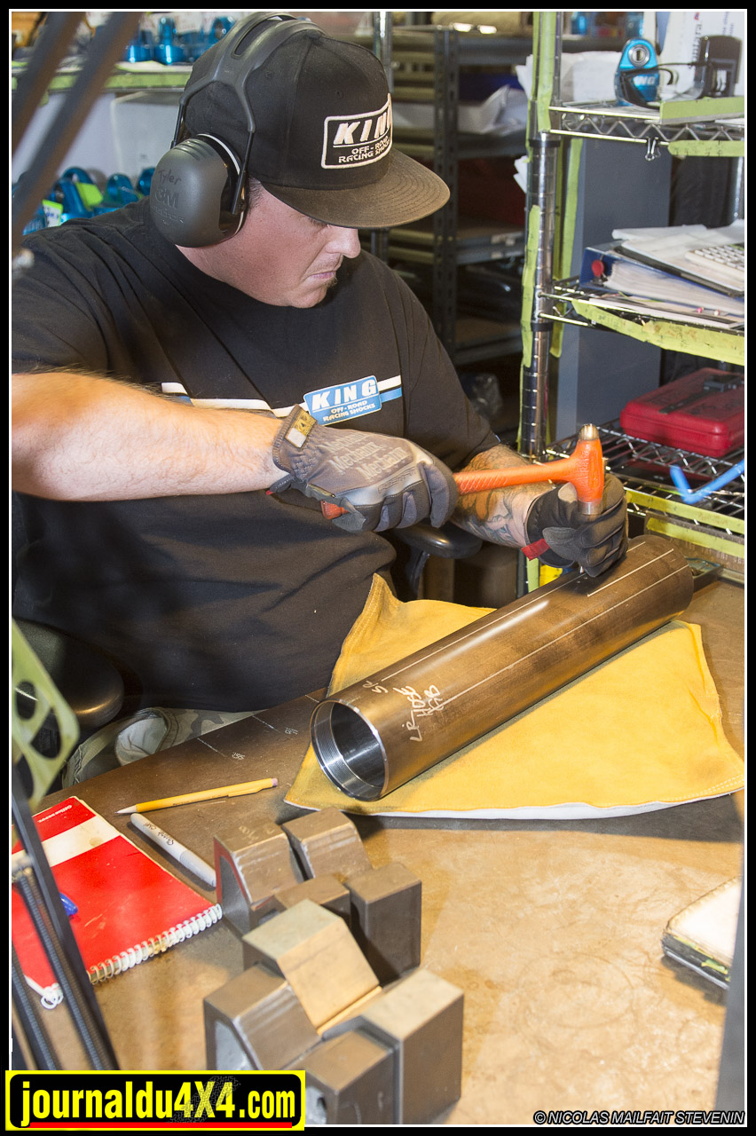 Here, this worker is marking on a shock body, the different locations where the bypass tubes are going to be installed.