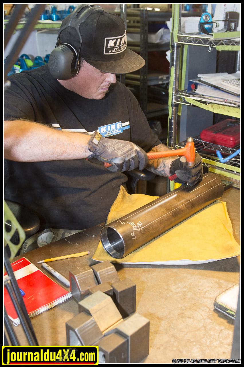 ici cet ouvrier marque les différents points sur le corps d'amorttisseurs où devront être montés les bypass