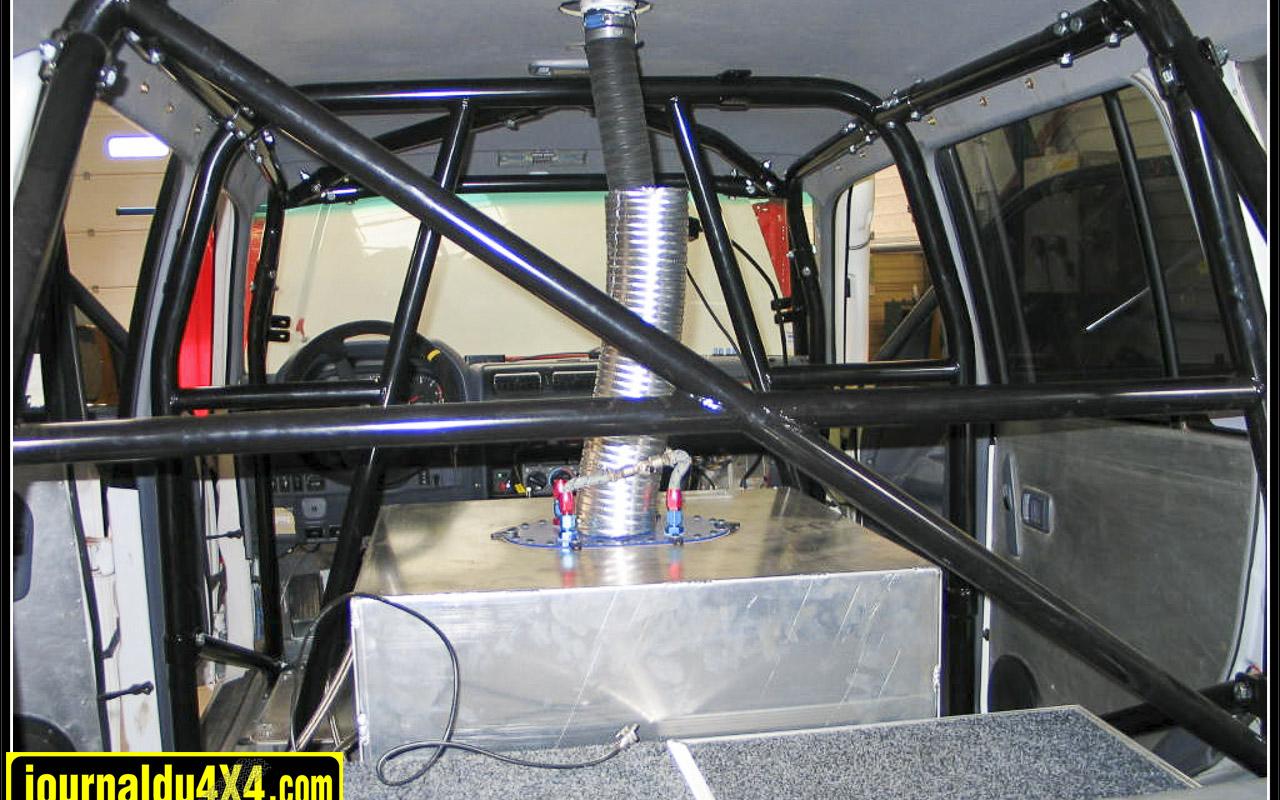 L'habitacle se fait lui aussi T2 avec un arceau LMT, des sièges baquets Sparco et harnais Sabelt, extincteur manuel, intercom Stilo, réserves d'eau, marteau brise glace et manomètre de pression des pneus de chaque côté.